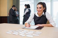 Smiling woman at welcome desk - stock photo