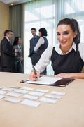 Happy woman at welcome desk - stock photo