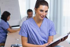 Stock Photo of Nurse standing with clipboard