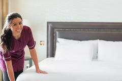 Hotel maid making up the bed Stock Photos