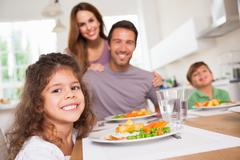 Stock Photo of Family smiling at the camera at dinner table