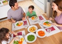 Family smiling around a healthy meal - stock photo