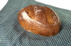 fresh baked loaf of sourdough rye bread on cloth - stock photo
