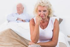 Discouraged old woman sitting on the bed - stock photo