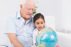 Granddaughter and grandfather with globe Stock Photos