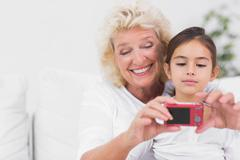 Granddaughter and grandmother taking pictures - stock photo