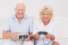 Aged couple playing video games Stock Photos