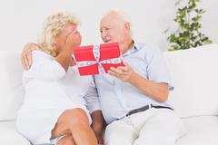 Old man offering a gift to the elderly woman - stock photo