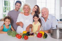 Multi-generation family cutting vegetables together - stock photo