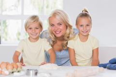 Family smiling at the camera with the baking tools - stock photo