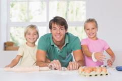 Smiling family with baking tools - stock photo