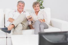 Old couple watching TV with legs crossed - stock photo
