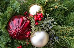 christmas arrangement with greens and ornaments - stock photo