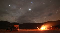Stock Video Footage of Country Campfire Timelapse Under Stars, Planets, and Clouds in Desert