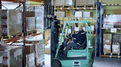 Forklift truck driver moving large boxes around a warehouse Stock Footage