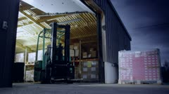 A worker drives a forklift truck out of a warehouse at night Stock Footage