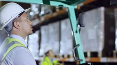 A forklift truck driver and his co-worker are working in a warehouse at night Stock Footage