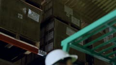 A forklift truck driver and his co-worker are working in a warehouse at night - stock footage
