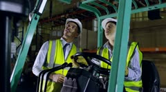 A forklift truck driver and her colleague are working in a warehouse at night - stock footage