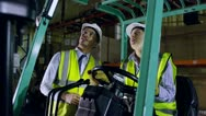 Stock Video Footage of A forklift truck driver and her colleague are working in a warehouse at night