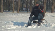 Stock Video Footage of Man Talking on the Phone while Sitting on a Sledge in Snow, Winter Season
