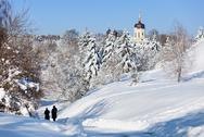 Beautiful winter landscape with snow covered firs and old church Stock Photos