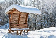 wooden awning bench covered by hard snow - stock photo