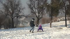 Mother Pulls her Child on Sleigh, Family Playing in Snow, Children, Winter Stock Footage