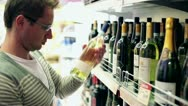 Young man choosing wine in the shop, steadycam shot Stock Footage