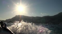 Sun, mountains and a town captured while on boat at sea Stock Footage