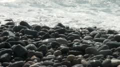 Shiny rocks at the shore of the sea reflect the sun Stock Footage