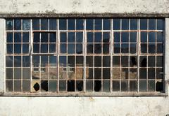broken windows in a derelict building about to be demolished. - stock photo