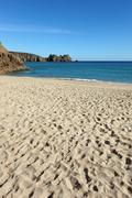 Porthcurno sandy beach and logan rock in cornwall uk. Stock Photos