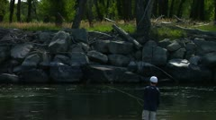 Young Boy fly casting into Yellowstone River Stock Footage