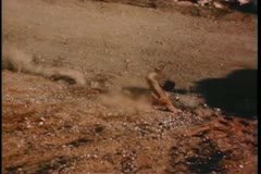 Man falling down hill onto dirt road - stock footage