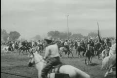 Cowboys on horseback prancing around  before rodeo Stock Footage