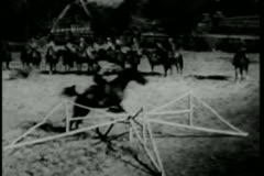 Cowboys on horseback jumping fence in a show ring Stock Footage
