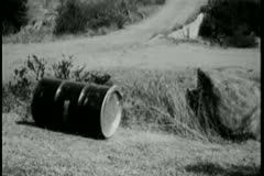 Oil drum rolling down hill Stock Footage