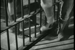 Low section of two people stomping feet in prison Stock Footage