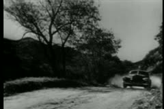 1940s car driving on shoulder of dusty country road - stock footage