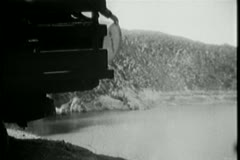 Man throwing oil drums from truck into the river Stock Footage