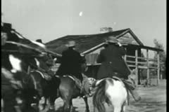 Group of men on horses riding towards house Stock Footage