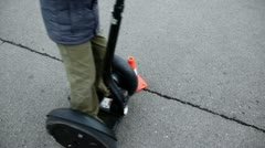 Young boy rides on segway around striped orange cone at asphalt Stock Footage
