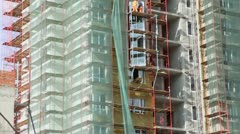 Workers stand on scaffold and set windows at construction site - stock footage