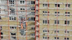 Workers stand on scaffold and set windows at construction site Stock Footage