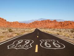 Route 66 pavement sign with red rock mountains Stock Photos