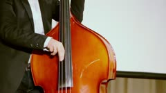 Man plays on contrabass on stage near screen during concert Stock Footage