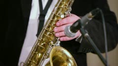 Musician in suit plays on saxophone in microphone on stage Stock Footage
