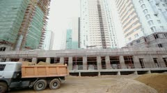 Truck rides backward at construction site of dwelling complex Stock Footage