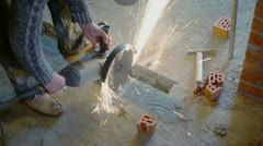 Man saws metalware by circular saw and hammer lays near on floor Stock Footage